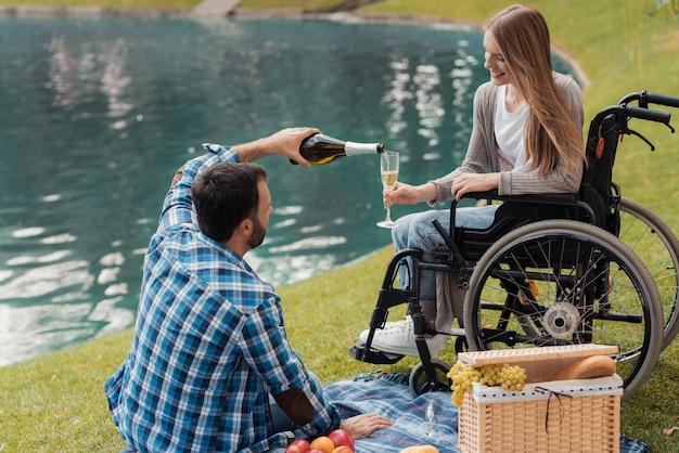 De man zit op een deken en giet een vrouw een glas champagne