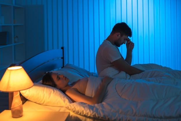 De man zit op het bed met hoofdpijn in de buurt van slapende vrouw. nachttijd