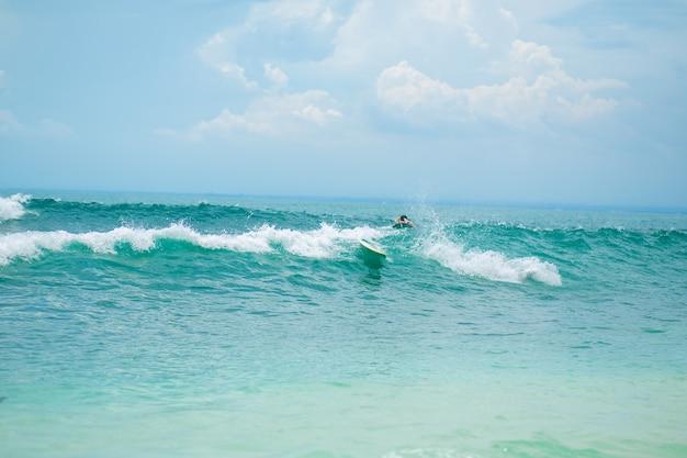 De man zwemt op de surfplank in de oceaan. gezonde actieve levensstijl in de zomervakantie.