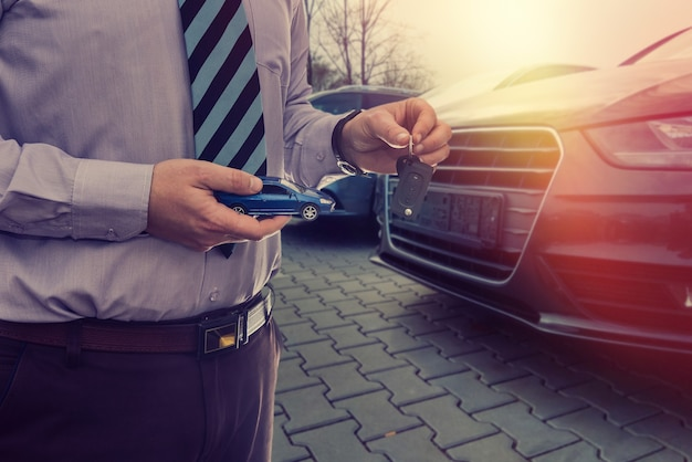 De manager accepteert de bestelling voor de verkoop van een nieuwe auto in de showroom.