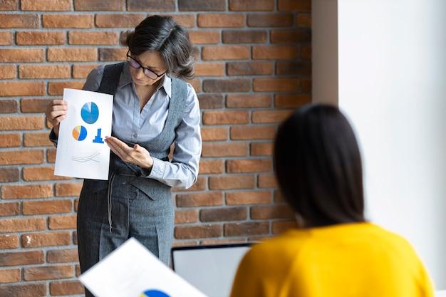 De manager op kantoor toont de verkoopgrafieken aan de ondergeschikte