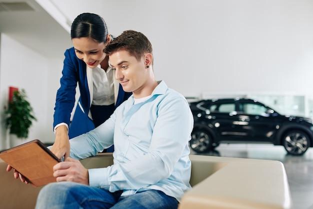 De manager van de dealer en de klant kijken naar auto's in de online catalogus op tabletcomputer