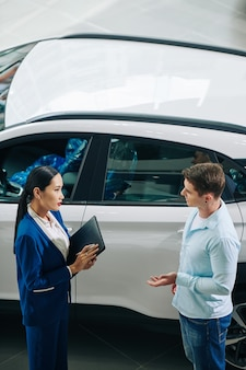 De manager van de dealer praat met de klant en vraagt naar zijn auto-voorkeuren en wensen
