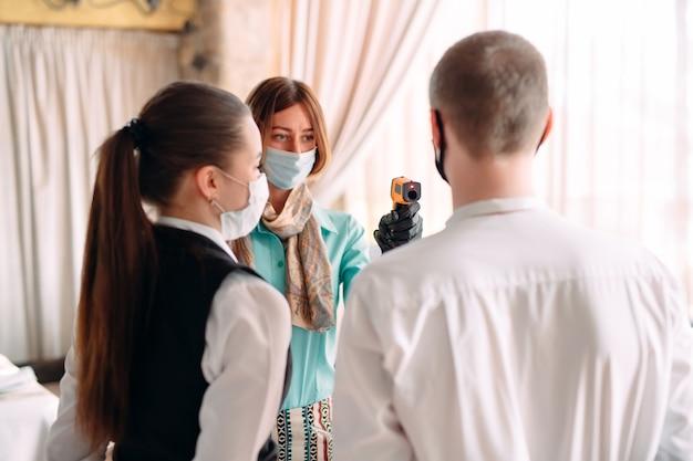 De manager van een restaurant of hotel controleert de lichaamstemperatuur van het personeel met een warmtebeeldcamera.