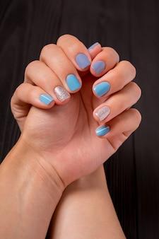 De manicure, blauw met zilveren kleur, geïsoleerd op een zwarte houten achtergrond