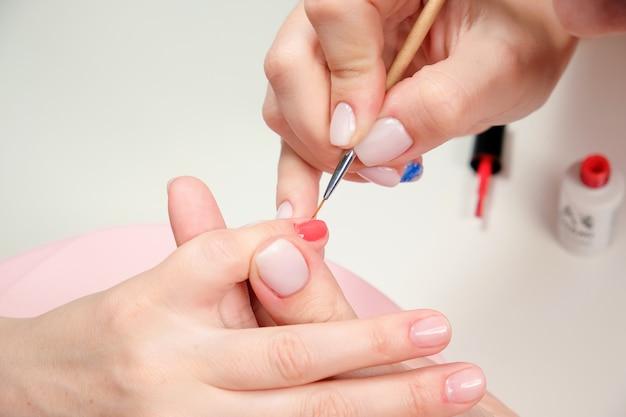 De manicuremeester brengt in een schoonheidssalon een glanzende nagellak aan op de nagels van de klant.