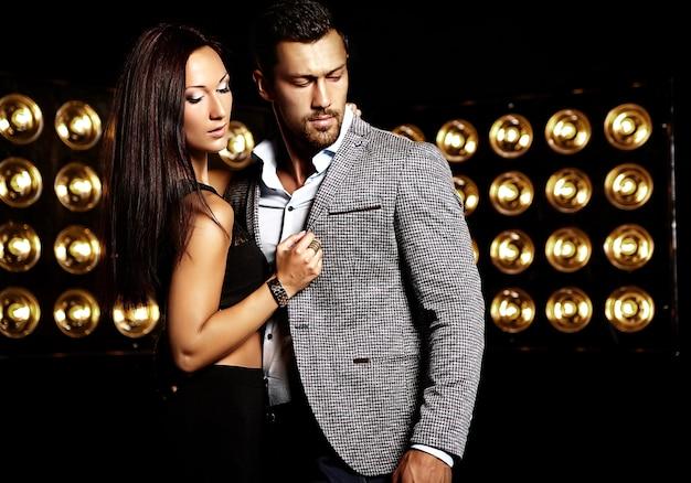 De manierfoto van de knappe elegante man in kostuum met het mooie sexy vrouw stellen op de zwarte achtergrond van studiolichten