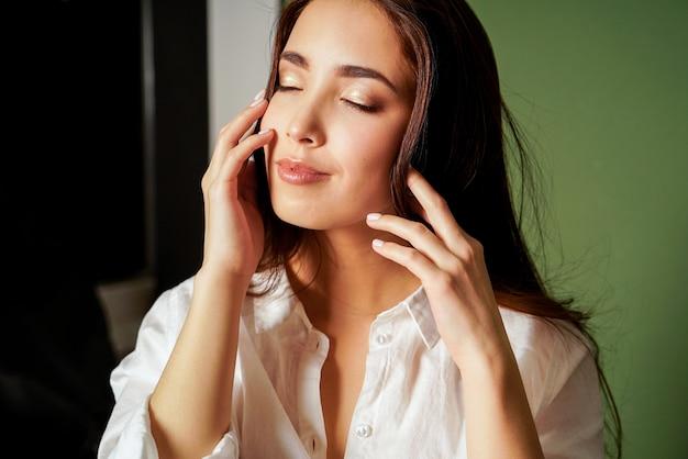 De manierportret van de schoonheid van sensuele sluitende ogen aziatische jonge vrouw met donker lang haar in wit overhemd