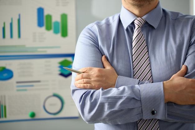 De mannelijke arn gekruiste pen van de zakenmangreep op wit raadsprobleem in bureauclose-up.