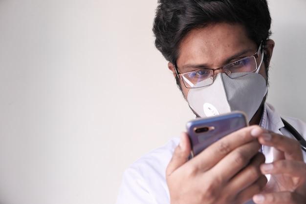 De mannelijke arts in witte laag gebruikt een modern smartphoneapparaat