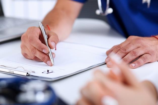 De mannelijke artsenhand schrijft recepttbureau worktable