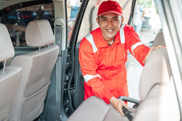De mannelijke autoreiniger draagt een glimlachend rood uniform tijdens het schoonmaken van de stofzuigerstoel in de auto