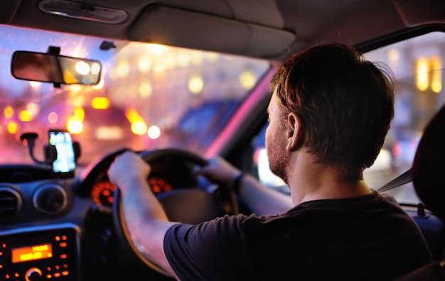 De mannelijke bestuurder berijdt een auto tijdens avondopstopping