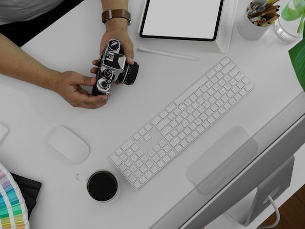 De mannelijke camera van de fotograafholding boven wit bureau met tablet, computerapparaat en andere levering