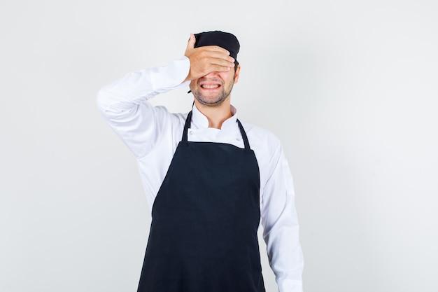 De mannelijke chef-kok die ogen behandelt dient uniform, schort in en kijkt opgewonden. vooraanzicht.