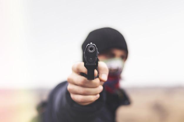 De mannelijke crimineel in actie van aanvallen met handpistool