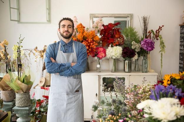 De mannelijke eigenaar die van de bloemwinkel vol vertrouwen camera bekijken
