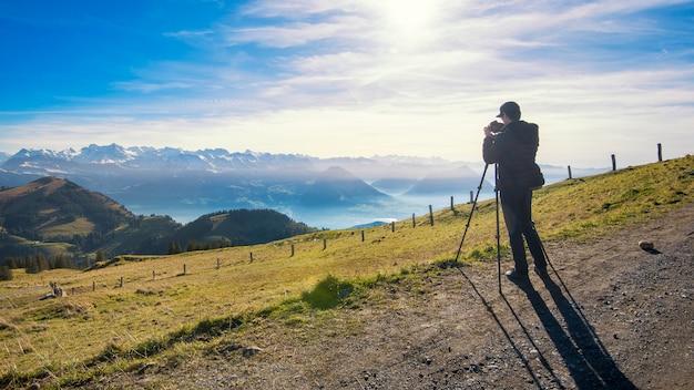 De mannelijke fotograaf ontspruit mening van rigi-berg in zwitserland