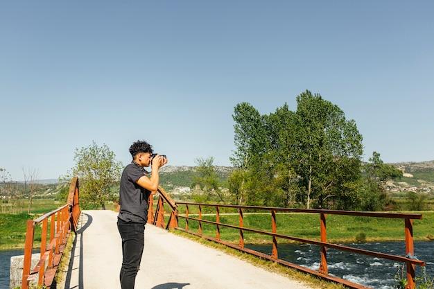 De mannelijke fotograaftoerist met camera schiet mooie aard