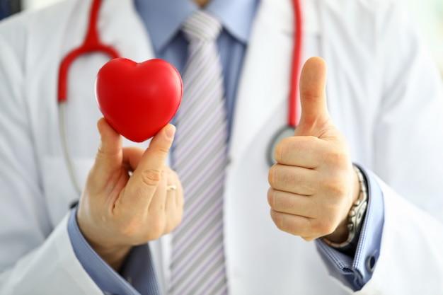 De mannelijke geneeskunde arts in greep rood stuk speelgoed hart en toont ok of goedkeuringsbord met duim op close-up. cardio-therapeut, arts maakt cardiale fysieke hartslagmeting, aritmieconcept