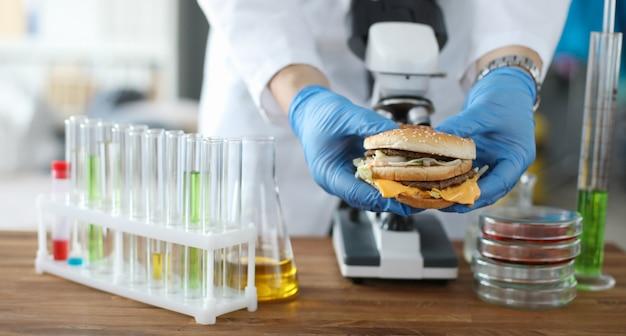 De mannelijke hamburger van de handgreep met blauwe beschermende handschoenen in hand