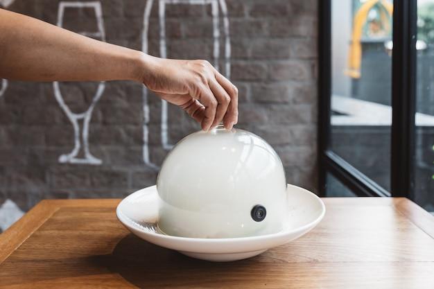 De mannelijke hand heft op glasglazen kap van een plaat met heet voedsel op restaurant op