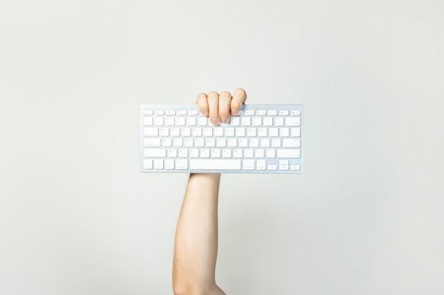 De mannelijke hand houdt een toetsenbord op een geïsoleerd licht