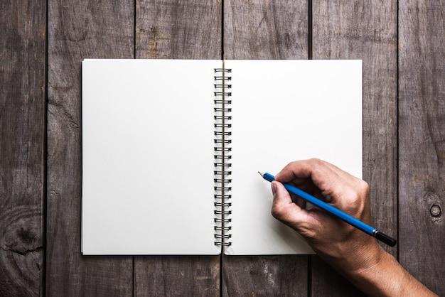 De mannelijke hand schrijft in een grote blocnote op een houten lijst