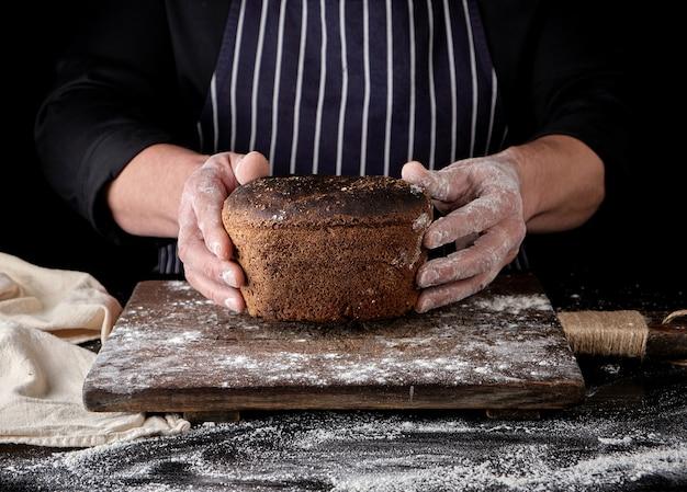 De mannelijke handen houden bruin gebakken roggebrood over houten raad met bloem