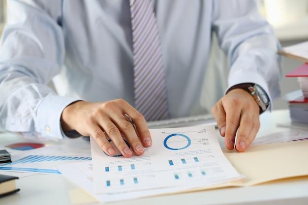 De mannelijke handen houden documenten met financieel
