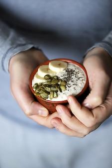 De mannelijke handen houden een kom yoghurt. een man met een lepel eet yoghurt met zaden. chia pudding met pompoenpitten en banaan.