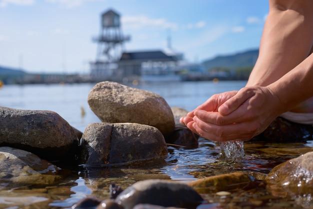 De mannelijke handen nemen schoon water van memphremagog-meer, provincie van quebec, canada op