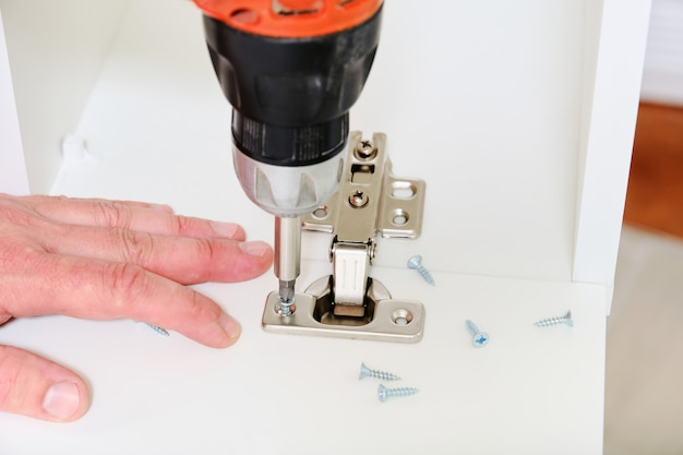 De mannelijke handen schroeften de meubilairscharnieren in keukenkast met draadloze schroevedraaierclose-up.