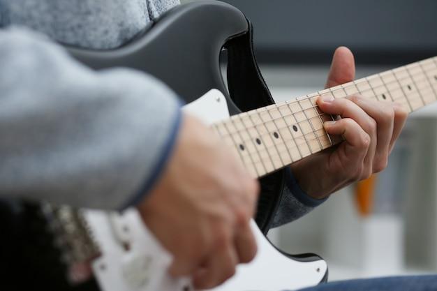 De mannelijke handen spelen en stemmen thuis de elektrische gitaar bezig is met muziek realiseert het luisteren genietend van grote het conceptenclose-up van de muzieknotatie