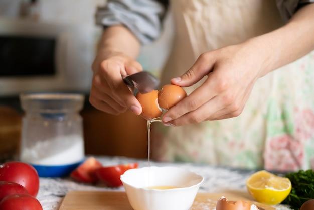De mannelijke handen van de kokbakker breken ei terwijl voedselvoorbereiding
