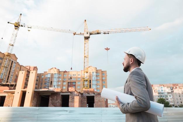 De mannelijke ingenieur draagt witte veiligheidshelm en houdt blauwdruk op bouwwerf