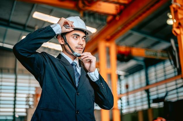 De mannelijke ingenieur-manager droeg een veiligheidshelm voordat hij de machines inspecteerde