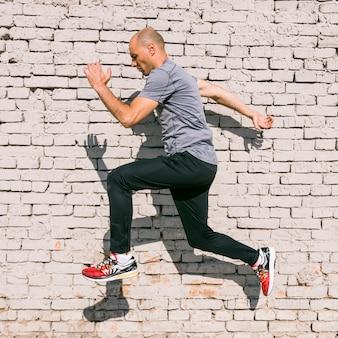 De mannelijke jonge mens die van de geschiktheidsatleet in lucht tegen witte geschilderde muur springt