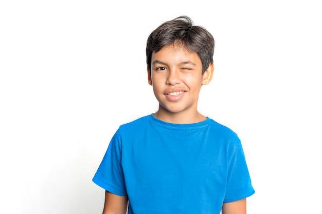 De mannelijke jongen in blauwe t-shirt dichte omhooggaand knipoogt portret op grijs