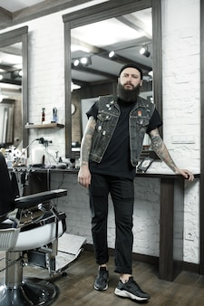 De mannelijke kapper tegen een kapperszaak