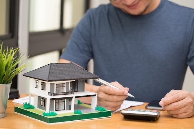 De mannelijke klant berekent huislening en rentevoet om droomhuis te kopen