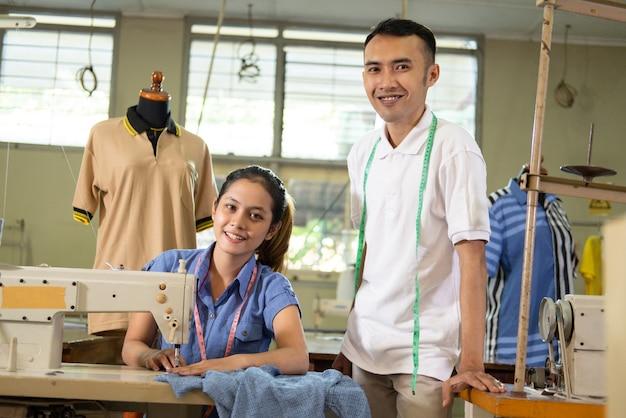 De mannelijke kleermaker staat naast de vrouwelijke kleermaker die een naaimachine gebruikt in de productieruimte voor kledingconvectie. stagiair student
