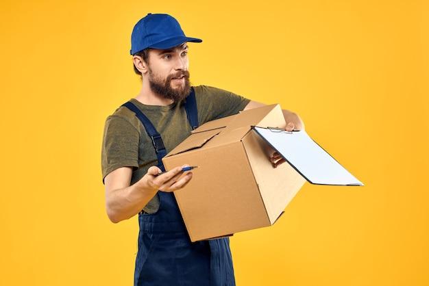 De mannelijke koerier van de werknemer levert dozen die documenten verpakken gele achtergrond.