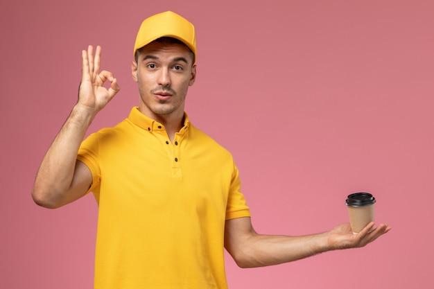 De mannelijke koerier van het vooraanzicht in geel uniform de kop van de holdingskoffie op de roze achtergrond
