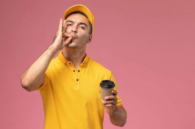 De mannelijke koerier van het vooraanzicht in geel uniform de leveringsbeker die van de holdingskoffie smakelijk teken op het roze bureau toont
