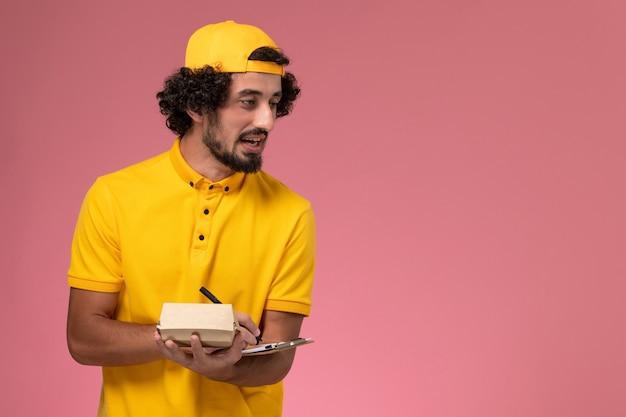 De mannelijke koerier van het vooraanzicht in geel uniform en cape met blocnote en weinig pakket van het leveringsvoedsel op zijn handen die nota's op roze achtergrond schrijven.