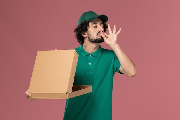 De mannelijke koerier van het vooraanzicht in groen uniform en cape die een lege doos van het leveringsvoedsel op roze achtergronddienstbaan uniforme levering houdt