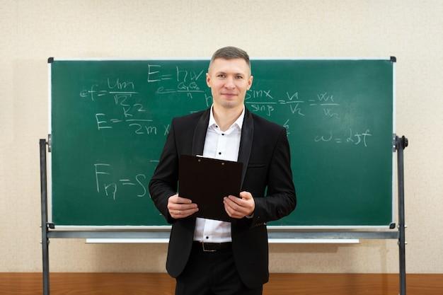 De mannelijke leraar gebruikte wit krijt om op het bord te schrijven om studenten in een klas les te geven
