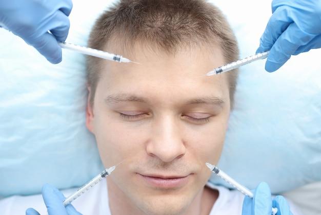 De mannelijke patiënt krijgt meerdere injecties in de gezichtshuid. cosmetologie voor mannen concept