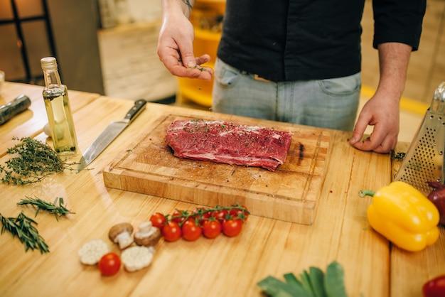 De mannelijke persoon bestrooit rauw vlees met kruiden